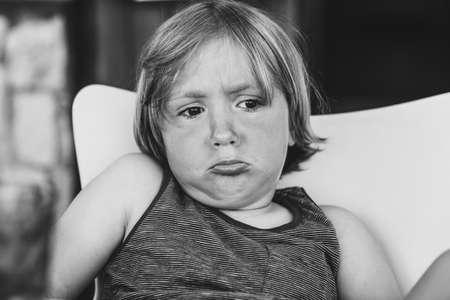 Close up portrait of sad toddler boy, black and white image