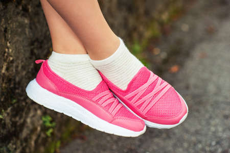 Close up image of pink modern sneakers wearing by a girl 版權商用圖片