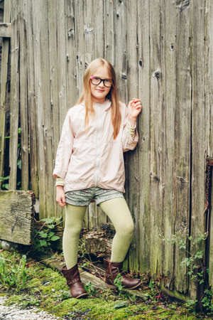 Outdoor fashion portrait of pretty little girl, wearing eyeglasses, pink mac, green tights and brown leather boots