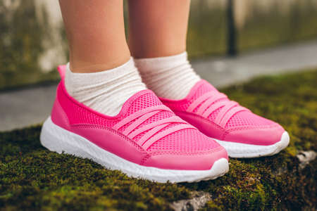 Close up image of pink modern sneakers wearing by a girl Foto de archivo