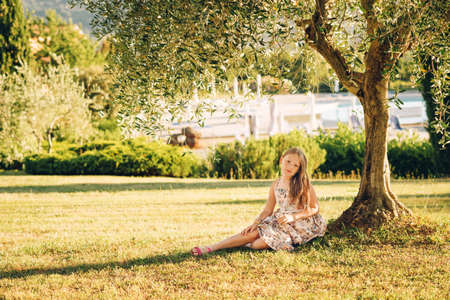 Outdoor portrait of adorable little girl resting in shade under green olive tree, summer vacation in Tuscany, Italy