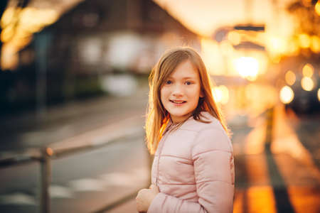 Outdoor portrait of cute little preteen girl in sunset light Foto de archivo