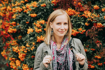Outdoor portrait of beautiful blond woman, posing next to bright orange scarlet firethorn berries (Pyracantha coccinea), wearing khaki color parka and pink scarf