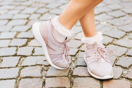 Woman wearing new comfy trainers and soft pink ruffle socks, close up image Stockfoto