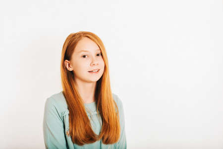 Studio shot of young preteen red-haired girl against white background 免版税图像