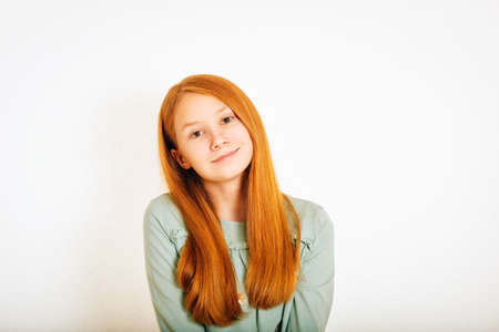 Studio shot of young preteen red-haired girl against white background Banco de Imagens