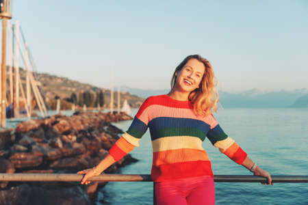 Beautiful woman resting by the lake at sunset on warm evening, wearing colorful pullover 写真素材