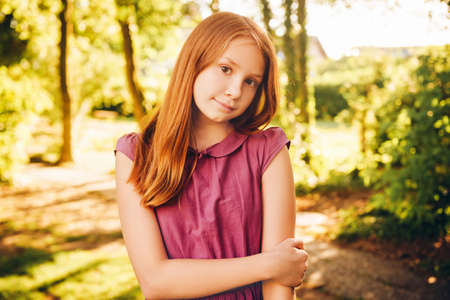 Outdoor portrait of 10-12 year old girl in summer park