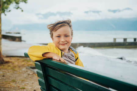 Cute little boy resting on a bench by the lake on a very windy day, watching waves, wearing yellow rain coat. Image taken on lake Geneva, Lausanne, Switzerland