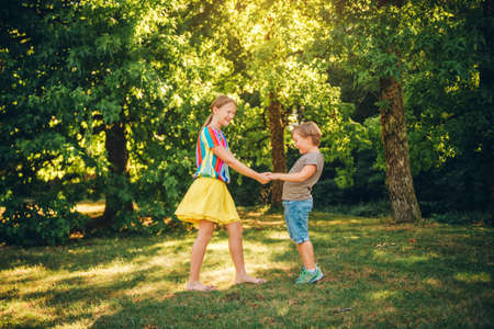 Group of two children playing together in summer park, holding hands, spinning around together