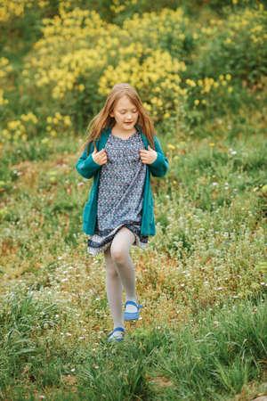 Ritratto di primavera all'aperto di una ragazza carina di 6-7 anni che gioca in un campo di fiori gialli, indossa un abito, un cardigan verde e una calzamaglia grigia