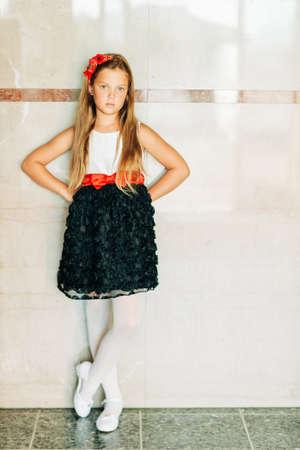 Ritratto di giovane modella che indossa abito di rose bianche e nere con cintura rossa