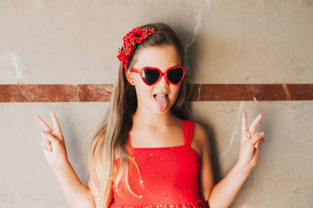 Funny portrait of pretty little girl wearing red dress and heart shaped sunglasses, pulling tongue