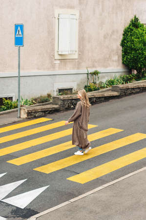 Fashion woman crossing the roadm wearing long knitted cardigan