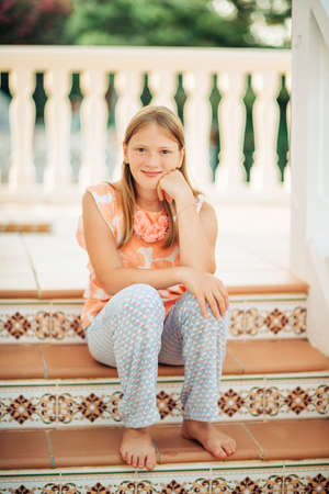 Outdoor portrait of beautiful young girl sitting on stairs