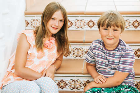 Outdoor summer portrait of two funny kids, small brother and big sister, siblings love