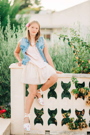 Outdoor summer portrait of young kid girl sitting on a fence, wearing denim vest and tutu skirt Foto de archivo