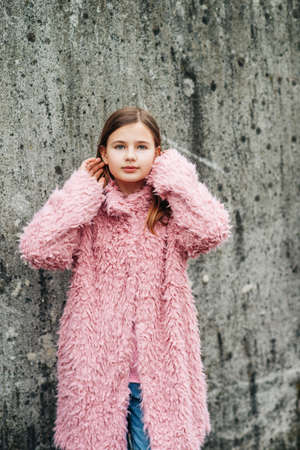 Outdoor fashion portrait of young girl wearing pink faux fur coat, street style Stok Fotoğraf
