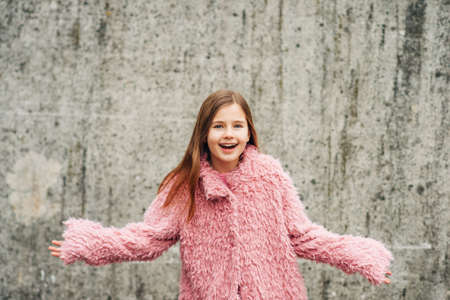 Outdoor portrait of excited little girl wearing faux fur pink coat, posing against grey city wall, arms wide open