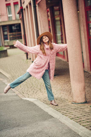 Outdoor fashion portrait of young girl wearing pink faux fur coat, street style Фото со стока - 116821723