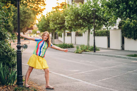 Summer portrait of pretty kid kid girl posing outdoors, wearing yellow skirt and colorful blouse