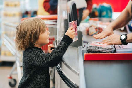Little boy buying fruits in a food store, holding 20 chf bill Фото со стока - 118985120