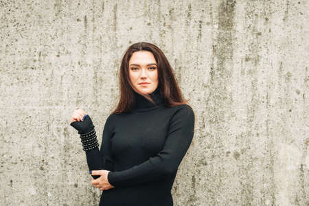 Outdoor portrait of young 35 year old woman with long dark hair, wearing black turtle neck dress