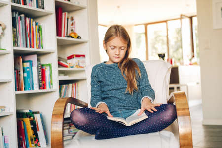 Cute little girl sitting in a white chair at home and reading a book Imagens