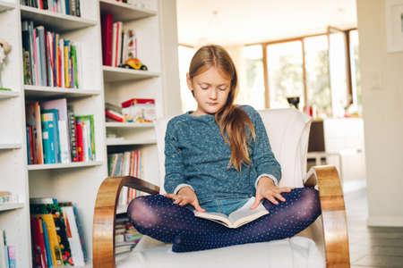 Nettes kleines Mädchen, das zu Hause in einem weißen Stuhl sitzt und ein Buch liest