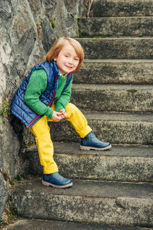 Outdoor fashion portrait of adorable little 4 year old boy, wearing blue waistcoat and boots, yellow trousers and green pullover 写真素材