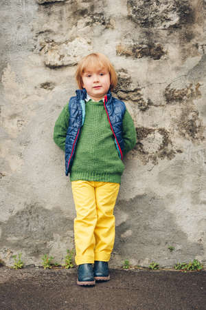 Outdoor fashion portrait of adorable little 4 year old boy, wearing blue waistcoat and boots, yellow trousers and green pullover Zdjęcie Seryjne