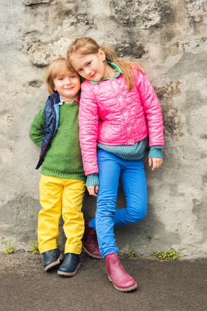 Outdoor portrait of two little kids, brother and sister, wearing colorful clothes