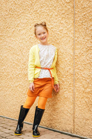 Fashion portrait of a cute little girl of 7 years old, wearing blouse, yellow jacket, orange skirt and black rain boots Stock Photo