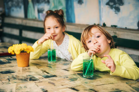 Two cute kids drinking green mint syrup in a cafe, wearing yellow clothes Фото со стока