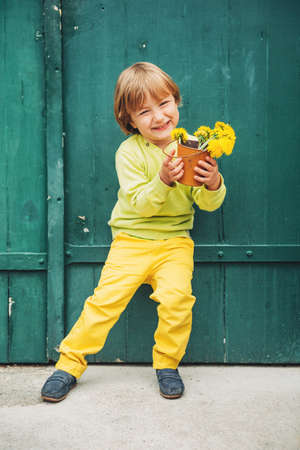 Outdoor portrait of a cute little boy, wearing yellow pullover and trousers and blue moccasins, standing by the green wooden door, holding bucket with flowers dandelions