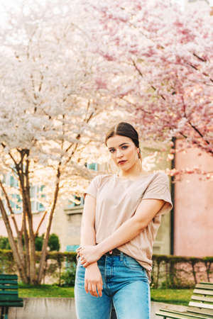 Outdoor spring portrait of young 18-20 year old girl posing in a city