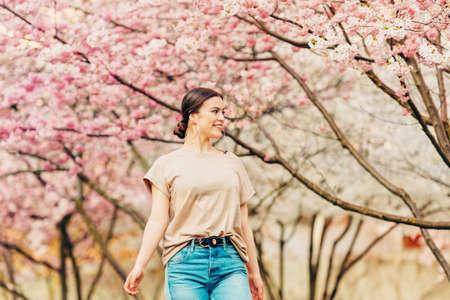 Outdoor portrait of beautiful 18-20 year old girl posing in blooming garden