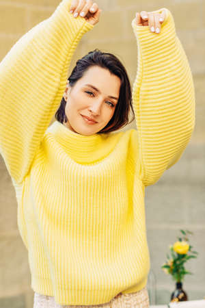 Outdoor portrait of beautiful woman with dark hair wearing yellow pullover, arms up Stock Photo