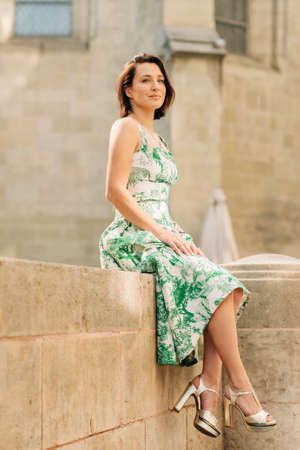 Outdoor fashion portrait of beautiful woman with dark hair, wearing long vintage styled green dress, posing on the city street, sitting on the wall