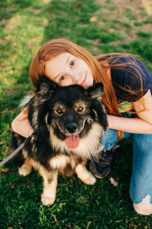 Outdoor portrait of cute red-hired kid girl hugging her dog Banque d'images