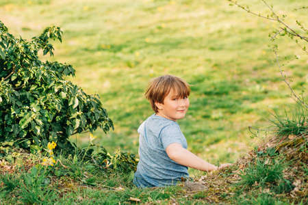 Cute little boy playing in summer park, green nature background, sitting on the bright green grass, looking back over the shoulder