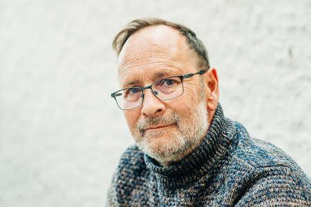 Outdoor-Porträt eines 50-jährigen Mannes mit braunem Pullover und Brille