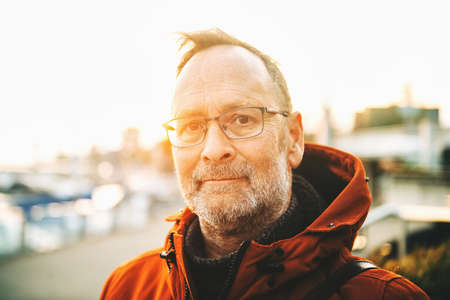 Outdoor portrait of middle age man wearing eyeglasses and orange winter jacket