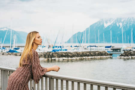 Outdoor portrait of young woman admiring beautiful lake, wearing brown dress. Image taken on Lake Geneva, Lausanne, Switzerland