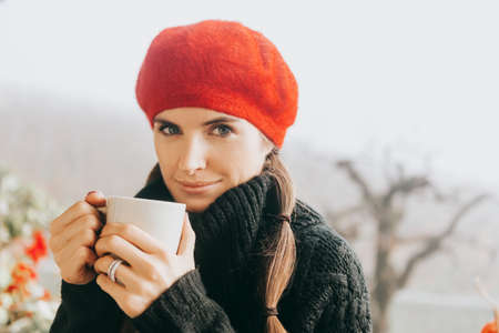 Close up portrait of young woman drinking hot tea on the balcony on a cold foggy daym wearing warm pullover and red beret 版權商用圖片