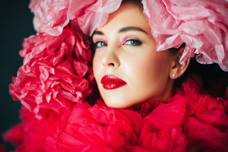 Close up portrait of beautiful young model with bright fashion makeup, wearing big pink fluffy collar, covered with decorative paper flowers Stockfoto