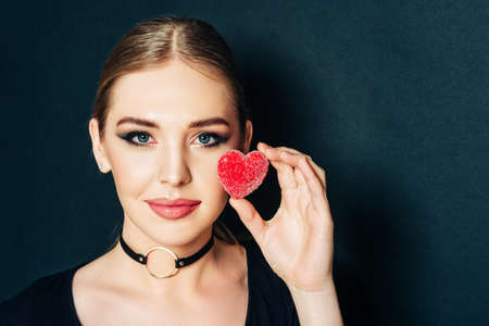 Close up studio portrait of beautiful young woman holding red heart next to face, black background Imagens