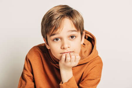 Studio shot of handsome 10 year old boy with blond hair, wearing brown hoody, posing on white background