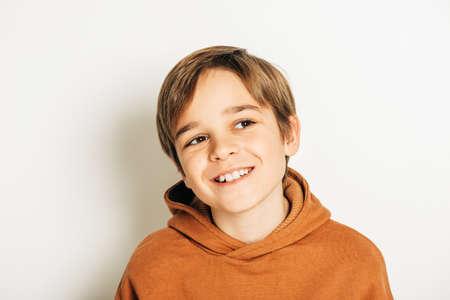 Studioaufnahme eines hübschen 10-jährigen Jungen mit blonden Haaren, der einen braunen Kapuzenpulli trägt, auf weißem Hintergrund posiert und nach oben schaut Standard-Bild