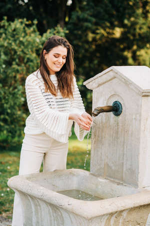 Outdoor fashion portrait of beautiful young woman playing with fountain, wearing white knitted sweater and denim trousers